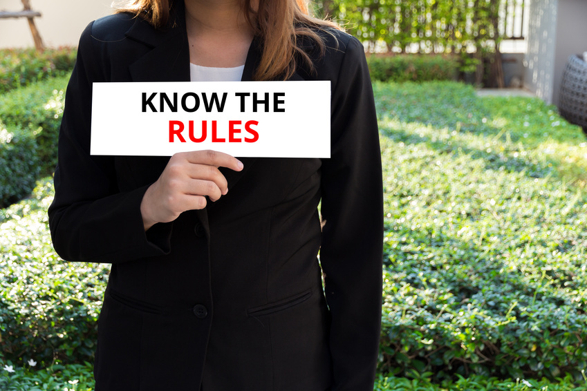 "Image: A woman holding a sign that reads, ""Know the rules"""